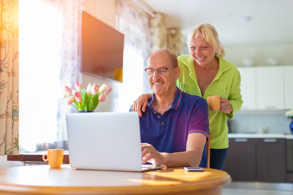 Senior couple looking at the lap top screen smiling and drinking coffee - elderly people video calling or talking by web camera - working at home, freelancing and having hobbies together concept